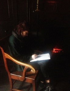 Jess writing her poem beside the Dove Cottage Fire